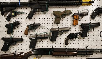 Seized firearms are displayed during a news conference Wednesday, Feb. 13, 2019, in Los Angeles. Federal prosecutors say they've dealt a blow to two Los Angeles gangs that have ties to the Mexican Mafia after charging dozens of suspected members with racketeering and drug and gun violations. (AP Photo/Jae C. Hong)