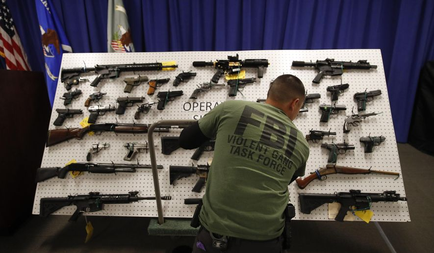 An FBI agent displays seized firearms before a news conference Wednesday, Feb. 13, 2019, in Los Angeles. Federal prosecutors say they've dealt a blow to two Los Angeles gangs that have ties to the Mexican Mafia after charging dozens of suspected members with racketeering and drug and gun violations. (AP Photo/Jae C. Hong)