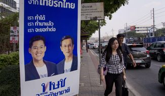 Pedestrians walk past an election poster promoting members of the Thai Raksa Chart political party in Bangkok, Thailand, Wednesday, Feb 13, 2019. The Thai Raksa Chart party, which took the unprecedented and ultimately unsuccessful step of nominating a member of the royal family as its candidate for prime minister, is fighting for its political life as the Election Commission says it has recommended that it be dissolved. (AP Photo/Gemunu Amarasinghe)