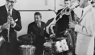 "FILE - In this July 5, 1960, file photo, Thailand's King Bhumibol Adulyadej, right, plays the saxophone during a jam session with legendary jazz clarinetist Benny Goodman, left, drummer Gene Krupa, second left, and trombonist Urbie Green in New York. The trombone world lost several greats in 2018 and a half-day event in Cleveland is planned to mark their legacies. Living trombone stars John Marcellus and Jiggs Whigham are headlining the Memorial Trombone Festival Saturday, Feb. 16, 2019, at Case Western Reserve University. Trombonists being memorialized are: Allen Kofsky, Edwin Anderson, Bill Watrous and Urban Clifford ""Urbie"" Green. (Bureau of the Royal Household via AP, File)"