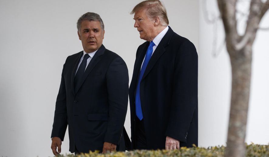 President Donald Trump walks with Colombian President Ivan Duque to a meeting in the Oval Office of the White House, Wednesday, Feb. 13, 2019, in Washington. (AP Photo/ Evan Vucci)