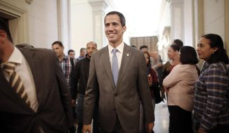 Venezuela' self proclaimed interim president Juan Guaido smiles as he arrives at the National Assembly, in Caracas, Venezuela, Wednesday, Feb. 13, 2019. Guaido said Wednesday that the National Assembly has appointed six executives to a transitional board for its PDVSA state-owned oil company and its U.S. subsidiaries, including Houston-based refiner Citgo. (AP Photo/Ariana Cubillos)