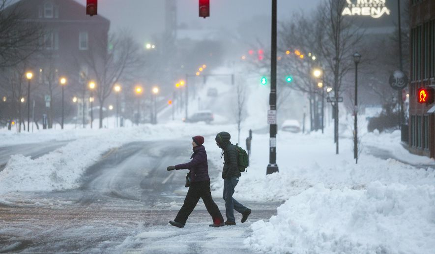 Pedestrians cross an intersection on Wednesday, Feb. 13, 2019, in Portland, Maine. A winter storm has buried northern New England with heavy snow and caused a slippery commute.  (Derek Davis/Portland Press Herald via AP)