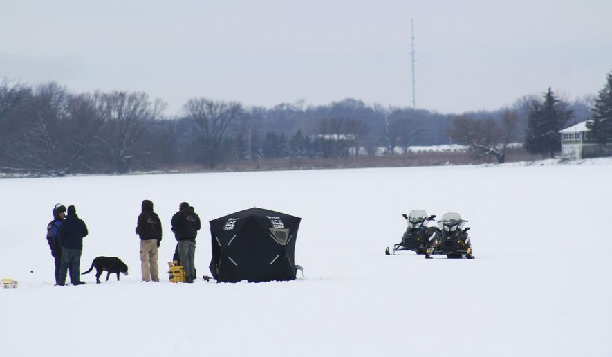 Snowmobilers and a dog enjoy snow and low temperatures on the frozen Eagle Lake in the Town of Dover, Tuesday, Feb. 12, 2019, in Racine County, Wis. (Adam Rogan/The Journal Times via AP)