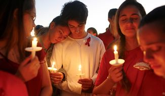 In this Thursday, Feb. 15, 2018, photo, students gather during a vigil at Pine Trails Park for the victims of the Wednesday shooting at Marjory Stoneman Douglas High School, in Parkland, Fla. Nikolas Cruz, a former student, was charged with 17 counts of premeditated murder last year. (AP Photo/Brynn Anderson) ** FILE **