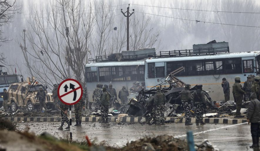 Indian paramilitary soldiers stand by the wreckage of a bus after an explosion in Pampore, Indian-controlled Kashmir, Thursday, Feb. 14, 2019. Security officials say at least 10 soldiers have been killed and 20 others wounded by a large explosion that struck a paramilitary convoy on a key highway on the outskirts of the disputed region's main city of Srinagar. (AP Photo/Umer Asif)