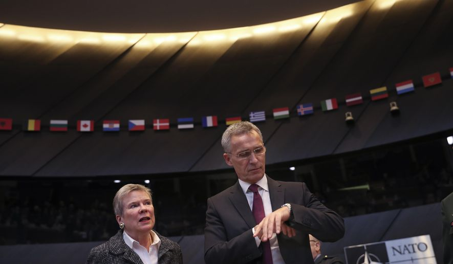 NATO Secretary General Jens Stoltenberg, right, looks at his watch before the start of a meeting of NATO defence ministers at NATO headquarters in Brussels, Wednesday, Feb. 13, 2019. (AP Photo/Francisco Seco)