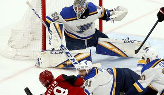 St. Louis Blues goaltender Jordan Binnington (50) makes a save on a shot by Arizona Coyotes center Clayton Keller (9) as Blues defenseman Robert Bortuzzo (41) and center Ryan O'Reilly (90) try to block the shot during the second period of an NHL hockey game Thursday, Feb. 14, 2019, in Glendale, Ariz. (AP Photo/Ross D. Franklin)