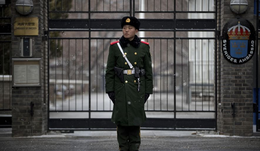 A paramilitary policeman stands guard at the gate of the Swedish Embassy in Beijing, Thursday, Feb. 14, 2019. The embassy said Thursday that Ambassador Anna Lindstedt has returned to Stockholm to be investigated by the country's foreign affairs ministry. She is not under criminal investigation. (AP Photo/Mark Schiefelbein)
