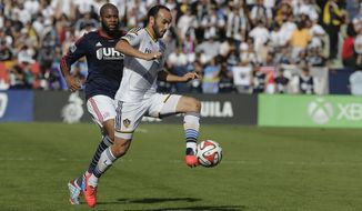 FILE - In this Dec. 7, 2014, file photo, Los Angeles Galaxy's Landon Donovan, right, controls the ball past New England Revolution's Andrew Farrell during the first half of the MLS Cup championship soccer match in Carson, Calif. Donovan doesn't look at it as coming out of retirement, since he never really considered himself retired. Donovan, the former U.S. national team and MLS star, will make his debut for the San Diego Sockers of the Major Arena Soccer League on Friday, Feb. 15, 2019, night against the Tacoma Stars. (AP Photo/Jae C. Hong,File)