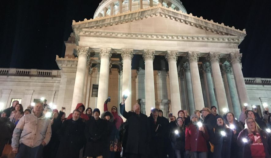 Teachers and union officials hold a candlelight vigil Wednesday, Feb. 13, 2019, outside the state Capitol in Charleston, W.Va. Inside, lawmakers continued to debate a complex education bill opposed by teachers. (AP Photo/John Raby)