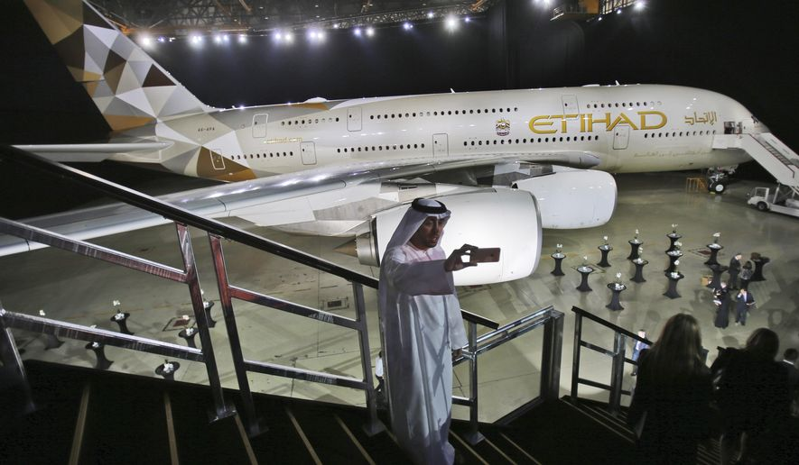 FILE - In this Dec. 18, 2014, file photo, an Emirati man takes a selfie in front of a new Etihad Airways A380 in Abu Dhabi, United Arab Emirates. Abu Dhabi-based Etihad Airways said Thursday, Feb. 14, 2019, that it has restructured planned airplane purchases from Airbus and Boeing as the government-owned carrier faces financial turbulence. (AP Photo/Kamran Jebreili, File)