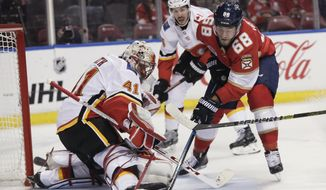 Florida Panthers left wing Mike Hoffman tries to score against as Calgary Flames goaltender Mike Smith blocks the puck during the first period of an NHL hockey game Thursday, Feb. 14, 2019, in Sunrise, Fla. (AP Photo/Brynn Anderson)