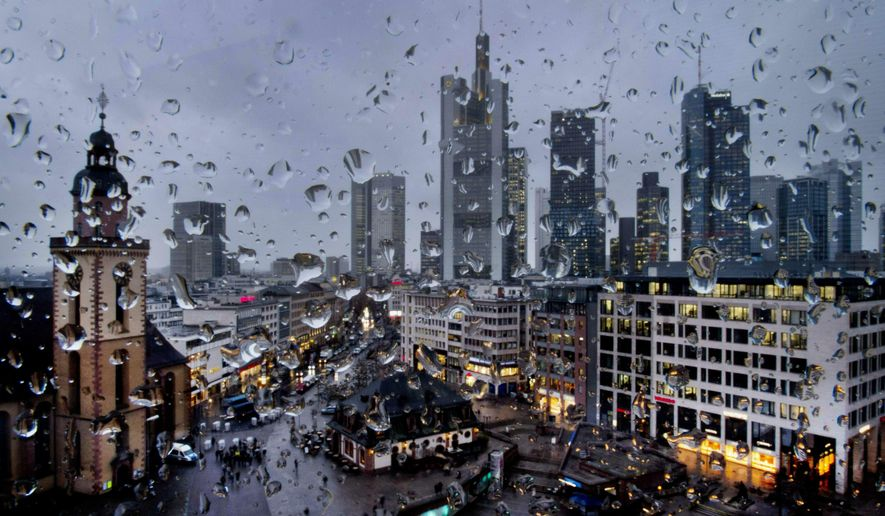In this Wednesday, Jan. 30, 2019, file photo, the buildings of the banking district are seen behind rain drops on a window in Frankfurt, Germany. Germany's economic growth has stagnated in the last three months of the year. (AP Photo/Michael Probst, file)