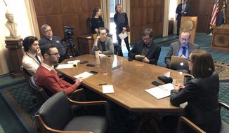 In this Thursday, Feb. 7, 2019 photo, Oregon Gov. Kate Brown, right, talks with reporters in her office in Salem, Ore. At a similar encounter on Thursday, Feb. 14, 2019, the Democratic governor described a lesson she learned from her stepdaughter wanting a dog while speaking about getting Republican lawmakers, who are in the minority in both the state Senate and House, on board as bills go through the Legislature. (AP Photo/Andrew Selsky)