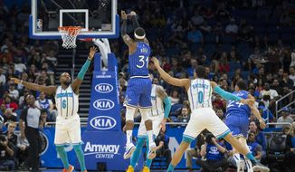 Orlando Magic guard Terrence Ross (31) scores against Charlotte Hornets guard Shelvin Mack (6) and forward Miles Bridges (0) during the first half of an NBA basketball game in Orlando, Fla., Thursday, Feb. 14, 2019. (AP Photo/Willie J. Allen Jr.)