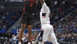 Houston's Armoni Brooks makes a basket as Connecticut's Sidney Wilson, right, defends during the first half of an NCAA college basketball game, Thursday, Feb. 14, 2019, in Hartford, Conn. (AP Photo/Jessica Hill)