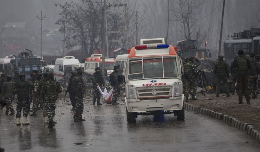 Indian paramilitary soldiers carry the remains of colleagues at the site of an explosion in Pampore, Indian-controlled Kashmir, Thursday, Feb. 14, 2019. Security officials say at least 10 soldiers have been killed and 20 others wounded by a large explosion that struck a paramilitary convoy on a key highway  on the outskirts of the disputed region's main city of Srinagar. (AP Photo/Dar Yasin)