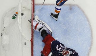 New York Islanders' Casey Cizikas, top, scores a goal against Columbus Blue Jackets' Sergei Bobrovsky, of Russia, during the first period of an NHL hockey game Thursday, Feb. 14, 2019, in Columbus, Ohio. (AP Photo/Jay LaPrete)