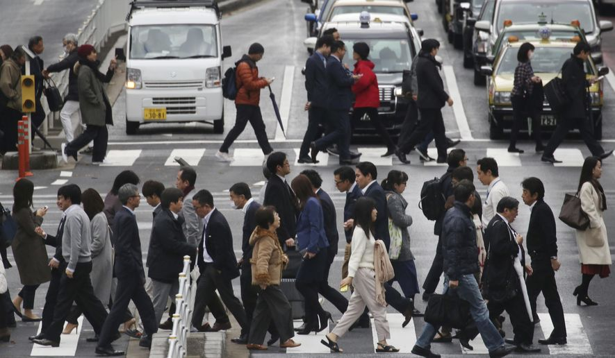 FILE - In this Dec. 12, 2018, file photo, people cross a street in Tokyo. Japan's economic growth for the October-December period rebounded from a slump the previous quarter, growing at an annual rate of 1.4 percent, according to preliminary government data released Thursday, Feb. 12, 2019. (AP Photo/Koji Sasahara, FIle)