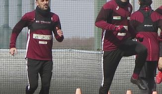 In this Jan. 21, 2019, photo, Vissel Kobe's Andres Iniesta, right, and David Villa, left, warm up during their team's training in Kobe, western Japan. Iniesta is hoping the addition of former Barcelona teammate Villa will lead to bigger and better things for his Japanese soccer team this season. (Kyodo News via AP)