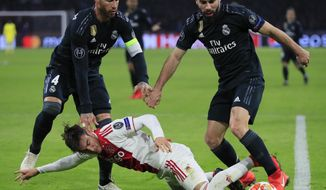 Ajax's Nicolas Tagliafico, center, is tackled by Real defender Dani Carvajal, right, and Real defender Sergio Ramos during the first leg, round of sixteen, Champions League soccer match between Ajax and Real Madrid at the Johan Cruyff ArenA in Amsterdam, Netherlands, Wednesday Feb. 13, 2019. (AP Photo/Peter Dejong)