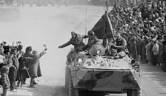 In this photo taken on Feb. 15, 1989, people and relatives greet Soviet Army soldiers driving on their armored personnel carriers after crossing a bridge on the border between Afghanistan and then Soviet Uzbekistan near the Uzbek town of Termez, Uzbekistan. When the Soviet Union completed its troops withdrawal from Afghanistan on this day, it was widely hailed as a much-anticipated end to a bloody quagmire, but public perceptions have changed and many Russians now see the 10-year Soviet war in Afghanistan as a necessary and largely successful endeavor. (AP Photo/Alexander Zemlianichenko)