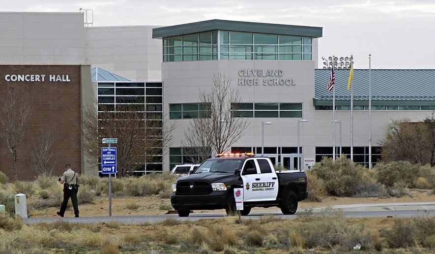 A Sandoval County Sheriff's Department deputy stands in front of Cleveland High School following a shots fired call in Rio Rancho, N.M., Thursday, Feb. 14, 2019. A shot was fired Thursday on the grounds of the suburban Albuquerque high school on the anniversary of the Parkland, Florida, high school massacre, but police and school officials said no one was injured and a suspect was in custody. (Adolphe Pierre-Louis/The Albuquerque Journal via AP)