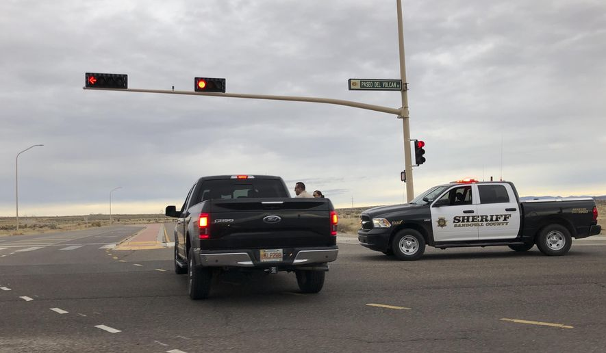 A Sandoval County sheriff's deputy stops a motorist near Sue Cleveland High School in Rio Rancho, N.M. on Thursday, Feb. 14, 2019. Rio Rancho police say a gunshot was fired at the high school in that Albuquerque suburb but that nobody was injured and that one person is in custody. (AP Photo/Russell Contreras)
