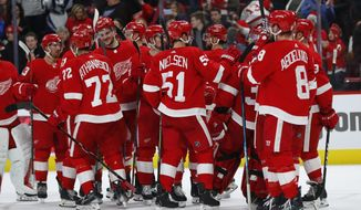 Detroit Red Wings players celebrate their 3-2 win over the Ottawa Senators after an NHL hockey game Thursday, Feb. 14, 2019, in Detroit. (AP Photo/Paul Sancya)