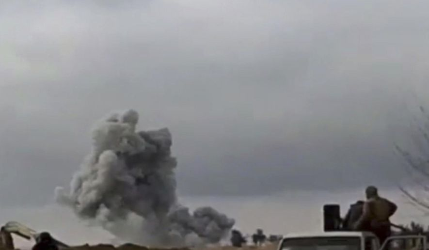 This frame grab from video provided on Tuesday, Feb. 12, 2019, by the Syrian Observatory for Human Rights, an opposition group, that is consistent with independent AP reporting, shows U.S.-backed Syrian Democratic Forces fighters looking at smoke rising from a shell that targeted Islamic State group militants, in the village of Baghouz, Deir El-Zour, eastern Syria. Fighting between U.S.-backed fighters and IS inflicted more casualties among people fleeing the violence in eastern Syria Tuesday where the extremists are on the verge of losing the last area they control. (Syrian Observatory for Human Rights via AP)