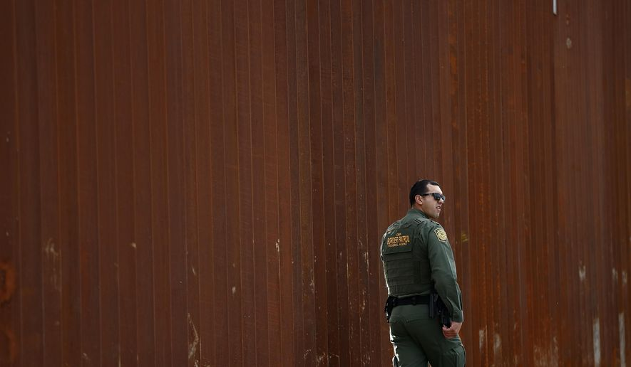 FILE - In this Jan 15, 2019, file photo, a U.S. Border Patrol agent walks in front of a section of newly-replaced border wall in San Diego. President Donald Trump would be taking an extraordinary step by declaring a national emergency to steer money to his promised border wall. He's making it sound quite ordinary. (AP Photo/Gregory Bull, File)