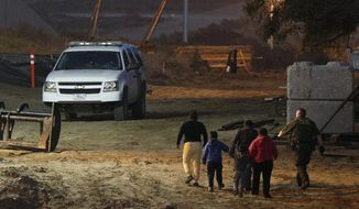 In this Dec. 3, 2018, file photo, migrants are escorted by a U.S. Border Patrol agent as they are detained after climbing over the border wall from Playas de Tijuana, Mexico, to San Ysidro, Calif. (AP Photo/Rebecca Blackwell, File)