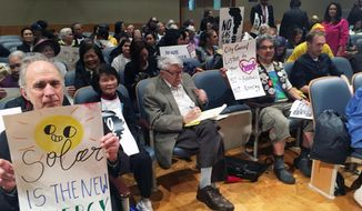 Opponents of a planned gas-fired power plant for eastern New Orleans are part of the crowd gathered for a city council committee hearing on Thursday, Feb. 14, 2019 in New Orleans. The hearing included discussions of a $5 million proposed penalty for Entergy New Orleans over the use of phony paid supporters who showed up at previous hearings in the project. (AP Photo/Kevin McGill)