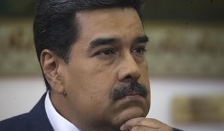 Venezuela's President Nicolas Maduro listens during an interview with The Associated Press at Miraflores presidential palace in Caracas, Venezuela, Thursday, Feb. 14, 2019. Even while criticizing Donald Trump's confrontational stance toward his socialist government, Maduro said he holds out hope of meeting the U.S. president to resolve an impasse over his recognition of opponent Juan Guaido as Venezuela's rightful leader. (AP Photo/Ariana Cubillos)