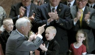 In this March 13, 2014 photo, Indiana Gov. Mike Pence, left, points to state Sen. Allen Paul, center, at an event at the Indiana War Memorial in Indianapolis where Pence signed a bill Paul sponsored that gave more military families access to the state's Military Family Relief Fund. Paul retired from the General Assembly in late 2014. The Indianapolis Star reports that a contract Paul later reached with the state's Department of Veterans Affairs may have violated state lobbying laws. (AP Photo/Rick Callahan)