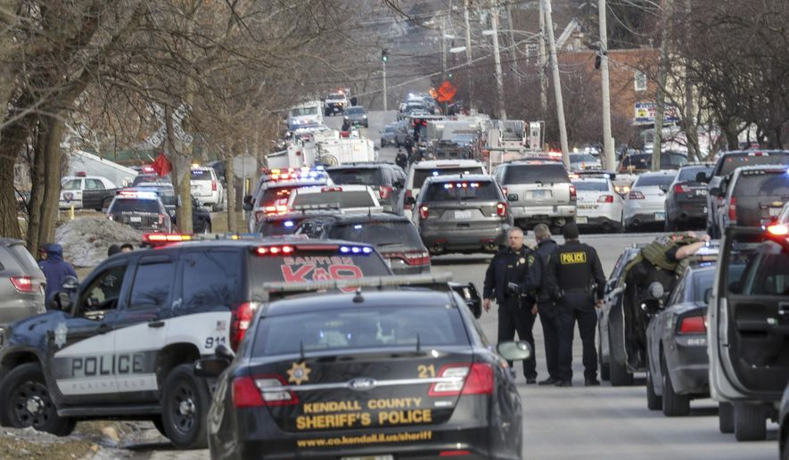 Law enforcement personnel gather near the scene of a shooting at an industrial park in Aurora, Ill., on Friday, Feb. 15, 2019. (Bev Horne/Daily Herald via AP)