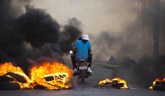 People on a motorcycle drive past a burning roadblock placed by anti-government protesters who are demanding the resignation of Haitian President Jovenel Moise, near the presidential palace in Port-au-Prince, Haiti, Wednesday, Feb. 13, 2019. (AP Photo/Dieu Nalio Chery)