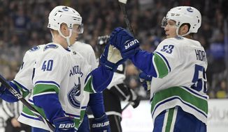 Vancouver Canucks center Elias Pettersson, left, celebrates his goals with center Bo Horvat during the first period of an NHL hockey game against the Los Angeles Kings Thursday, Feb. 14, 2019, in Los Angeles. (AP Photo/Mark J. Terrill)
