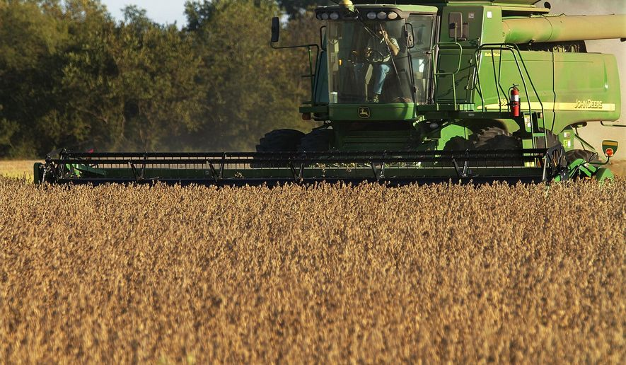 FILE - In this Sept. 30, 2010 file photo, central Illinois farmers harvest soybeans in Pleasant Plains, Ill.  Deere, a manufacturer that faces threats on both ends of a trade war, cited rising costs and anxious farmers,  in reporting a profit shortfall for the first quarter Friday, Feb. 15, 2019.  Shares bounced back from sharp premarket declines, however, on a relatively strong outlook, and hopes that tensions with China will receded in the coming year.  (AP Photo/Seth Perlman)