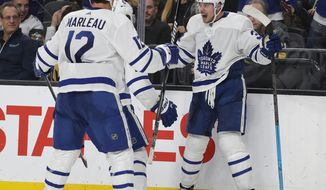 Toronto Maple Leafs center Auston Matthews, right, celebrates after scoring against the Vegas Golden Knights during the third period of an NHL hockey game Thursday, Feb. 14, 2019, in Las Vegas. (AP Photo/John Locher)