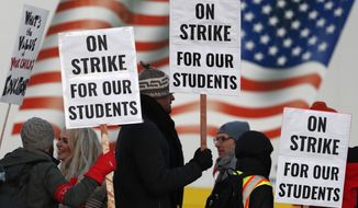 """FILE - In this Feb. 11, 2019, file photo, teachers carry placards as they walk a picket line outside South High School in Denver. The union representing Oakland, California teachers says it will issue a """"major announcement"""" Saturday, Feb. 16, 2019, about a potential strike, a day after a neutral fact-finding report was to be issued. Denver teachers ended a three-day walkout and returned to their classrooms Thursday, Feb. 14, 2019. (AP Photo/David Zalubowski, File)"""