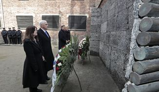 United States Vice President Mike Pence and his wife Karen Pence, left, stand with Poland's President Andrzej Duda and his wife Agata Kornhauser-Duda, right, in front of wreaths at a death wall during their visit at the Nazi concentration camp Auschwitz-Birkenau in Oswiecim, Poland, Friday, Feb. 15, 2019. (AP Photo/Michael Sohn)