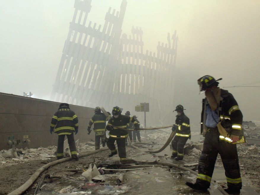 In this Sept. 11, 2001, file photo, with the skeleton of the World Trade Center twin towers in the background, New York City firefighters work amid debris on Cortlandt Street after the terrorist attacks. On Friday, Feb. 15, 2019, Rupa Bhattacharyya, the September 11th Victim Compensation Fund special master, announced that the compensation fund for victims of the Sept. 11, 2001, terror attacks will cut future payments by 50 to 70 percent because the fund is running out of money. (AP Photo/Mark Lennihan, File)