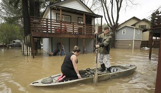 Residents of Sycamore Court flooded by Armstrong Creek, who declined to give their names, paddle out of high water from their apartment in Guerneville, Calif., Thursday, Feb. 14, 2019. Waves of heavy rain pounded California on Thursday, trapping people in floodwaters, washing away a mountain highway, triggering a mudslide that destroyed homes and forcing residents to flee communities scorched by wildfires last year. (Kent Porter/The Press Democrat via AP)