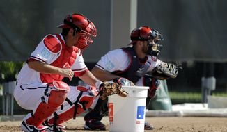Washington Nationals catchers Kurt Suzuki, left, and Yan Gomes work on a defensive drill during spring training baseball practice Saturday, Feb. 16, 2019, in West Palm Beach, Fla. (AP Photo/Jeff Roberson) **FILE**