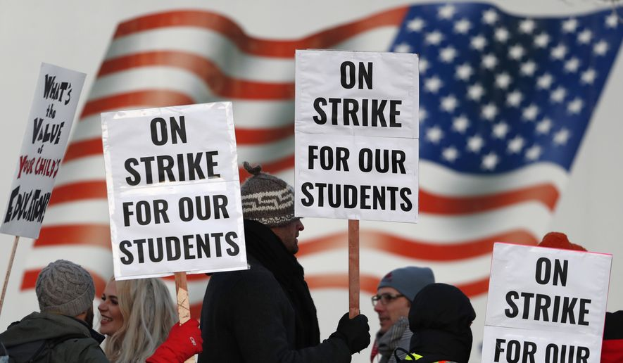 In this Feb. 11, 2019, file photo, teachers carry placards as they walk a picket line outside South High School in Denver. Oakland teachers say they will strike starting Thursday, Feb. 21. The union representing the 3,000 teachers announced the walkout Saturday, Feb. 16, making it the latest in a wave of educator activism that has swept the U.S. since last spring. (AP Photo/David Zalubowski, File)