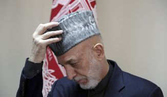 Former Afghan President Hamid Karzai adjusts his hat during an interview with The Associated Press in Kabul, Afghanistan, Saturday, Feb. 16, 2019. Karzai expressed fears that a previously unscheduled meeting between the Taliban and the United States in Pakistan on Monday risks engulfing Afghanistan into regional rivalries, as its neighbors and powerful Persian Gulf states jockey for influence in a post- U.S. Afghanistan. (AP Photo/Rahmat Gul)