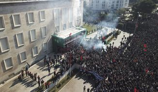 Opposition supporters take part in an anti-government rally in capital Tirana, Albania, Saturday, Feb. 16, 2019. Thousands of Albanian opposition supporters have clashed with police in an anti-government rally to protest what they says is a corrupt and inefficient Cabinet, asking for its resignation and early elections. (AP Photo/ Hektor Pustina)