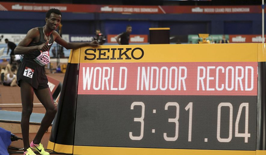 Ethiopia's Samuel Tefera poses next to teh time indicator, as he celebrates getting the mens 1500 metre World Indoor Record during the Muller Indoor Grand Prix in Birmingham, England, Saturday Feb. 16, 2019.  (David Davies/PA via AP)